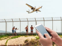 Women using smartphone. Top on blurred some people looking airport with old airplane Royalty Free Stock Image
