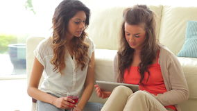 Women using tablet computer. On floor of living room stock video footage