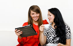 Women using tablet pc. Two young women using tablet pc Royalty Free Stock Image