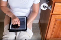 Women using toilet while surfing wireless internet device in bat Stock Image