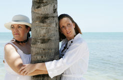 Women on Vacation. Two women on vacation in the tropics embracing a palm tree Royalty Free Stock Photo