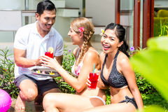 Women in vacation at Asian hotel pool with cocktails Royalty Free Stock Images