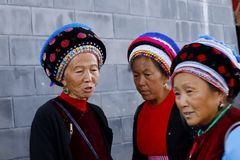Women from various ethnic minorities of Yunnan with their traditional clothes in the market of Zhoucheng village, Yunnan, China. Zhoucheng village, Yunnan, China stock image