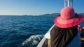 Women in veil and hat on front of boat with blue dark sea and island in distance stock photography