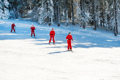 Women in vibrant red jackets skiing at the slope Stock Photo