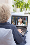 Women video call doctor x-ray. Rear view of a senior women sitting with notebook on the couch of her living room, having a video call with her doctor via the Royalty Free Stock Photography