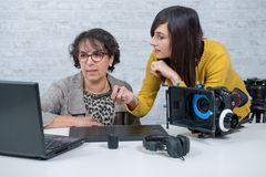 Woman video editor and young assistant using graphic tablet. A women video editor and young assistant using graphic tablet royalty free stock photography