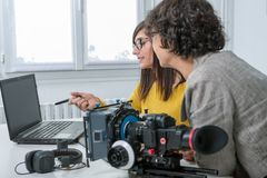 Woman video editor and young assistant using graphic tablet stock photo