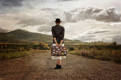 Women with vintage suitcase at old road. Photo in retro style Stock Images