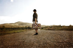 Women with vintage suitcase at old road. Photo in retro style Stock Photo