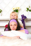 The woman in violet clothes with the girl lies on a floor Stock Photos