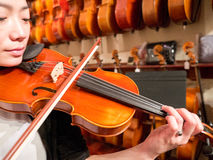Women Violinist Playing A Violin In A Music Store. Female violinist teacher and professional musician playing a violin for sale. Old world master craftsmanship Royalty Free Stock Photography