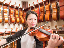Women Violinist Playing A Violin In A Music Store. Female violinist teacher and professional musician playing a violin for sale. Old world master craftsmanship Stock Photos