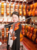 Women Violinist Playing A Violin In A Music Store. Female violinist teacher and professional musician playing a violin for sale. Old world master craftsmanship Stock Photo