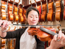 Women Violinist Playing A Violin In A Music Store. Female violinist teacher and professional musician playing a violin for sale. Old world master craftsmanship Stock Images