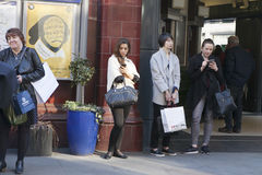 Women are waiting for friends near Covent Garden, buried in mobile phones Stock Photos