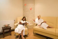 Women waiting at the spa. Two young women, wearing white robes, waiting in a lounge at the spa and reading magazines Stock Photos