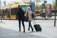 Women waiting with suitcase at the bus station in front of train station stock image