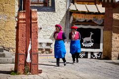 Women walk in the Songzanlin Monastery. Shangri-La, China - September 25, 2017: Women walk in the Songzanlin Monastery, built in 1679, is the largest Tibetan Stock Photos