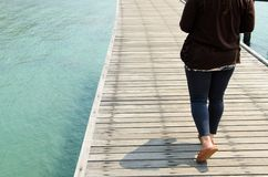 Women walk on wooden bridge. Women walk on brown wooden bridge at sea Stock Photography
