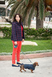 Women walking around town with dachshund dog Royalty Free Stock Photography