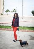 Women walking around town with dachshund dog Royalty Free Stock Image
