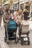 Women walking with baby carriages Royalty Free Stock Images