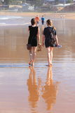 Women walking barefoot on beach. Two women, mother and daughter, talking and walking relaxed on their way home. Lifestyle in Australia at Avoca Beach, Central Royalty Free Stock Photos