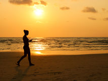 Women walking on the beach at sunset time. silhouette of the gir. L listen music on the beach Stock Images
