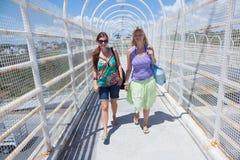 Women walking through bridge. Two young women walking through the bridge on a sunny day in Mexico Stock Photos