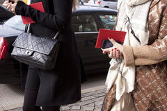 Women walking with designer purse and holding smartphone and invitation. Street style during new york fashion week stock image