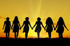 Women walking hand in hand. Silhouette of six young women, walking hand in hand