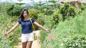 Women are walking and the hands touch the flowers in garden.  stock video