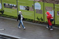 Women walking with hood during Raining day wet street, construction project in fischerinsel Royalty Free Stock Photos