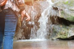 A women Walking with jeans and sneaker shoes and Waterfall background, concept travel, soft and select focus. Stock Image