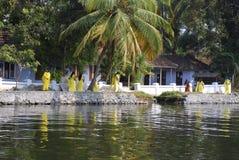 Women walking Kerala backwaters. Women in yellow saris walking next to the backwaters in Kerala, India Stock Photo