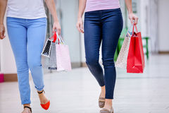 Women walking in mall with shopping bags royalty free stock photo