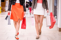 Women walking in mall with shopping bags royalty free stock image