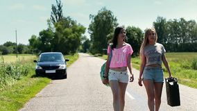 Women walking on road with rusty canister in hand stock footage