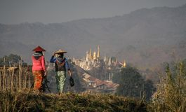 Women walking on the shore of Inle lake at the Nampan Market with a pagoda in the background, Inle Lake, Shan State, Myanmar Stock Photography