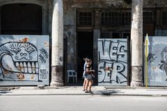 Young women walking in front of graffiti and morbid colonial architectur, Havana, Cuba stock images