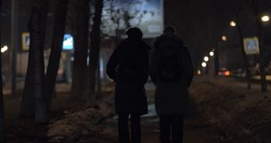 Women walking in the street and having friendly conversation. Back view of two women having a walk in evening winter city and talking friendly stock video