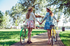 Women walking in the summer park holding hands looking in the sunset with their bikes stock images