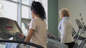 Women walking on treadmill in gym. Young woman walks at the treadmill and uses phone. Pretty brunette recreates after running. Elderly woman walks on running stock video footage