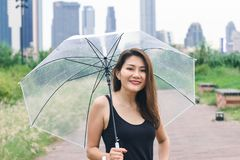 Women walking the umbrella  in the park royalty free stock image
