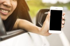 Women was sitting in the car.She was show smart phones. The mobile has a black space for your pictures and text.road trip, travel, Stock Images