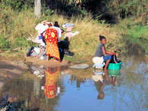 Women wash colorful clothes on the banks of a river, Madagascar Royalty Free Stock Photos