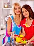 Women washing fruit at kitchen Royalty Free Stock Photography