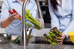 Women washing vegetables Stock Photo