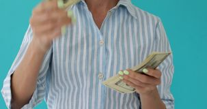 Women waste money. Closeup carefree woman wasting stack of much money, having a lot of hundred dollars blue background stock video footage